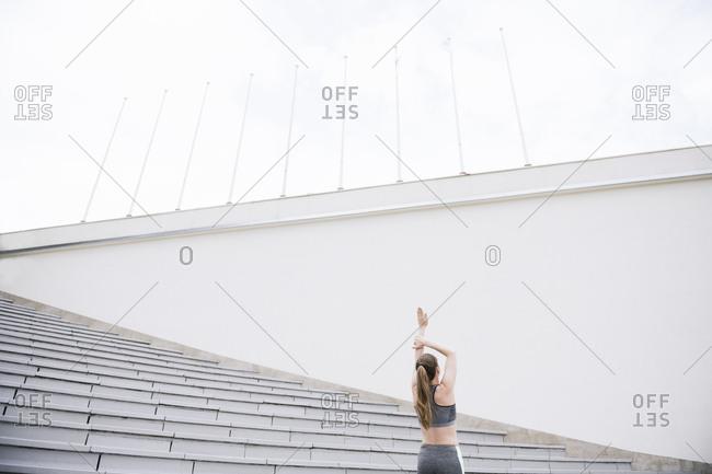 Rear view of woman raising arm- stretching on concrete bleachers