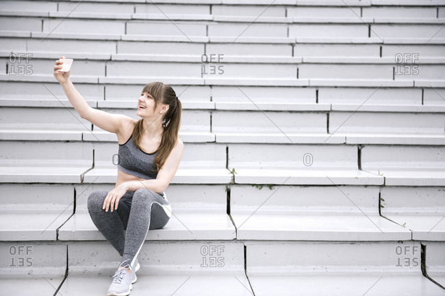 Young woman in sportswear sitting on concrete bleachers and making selfie