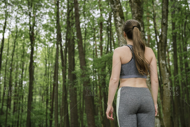 Rear view of young woman wearing sportswear standing in forest