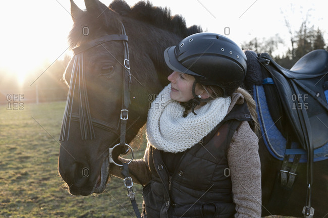 Smiling woman with horse at backlight