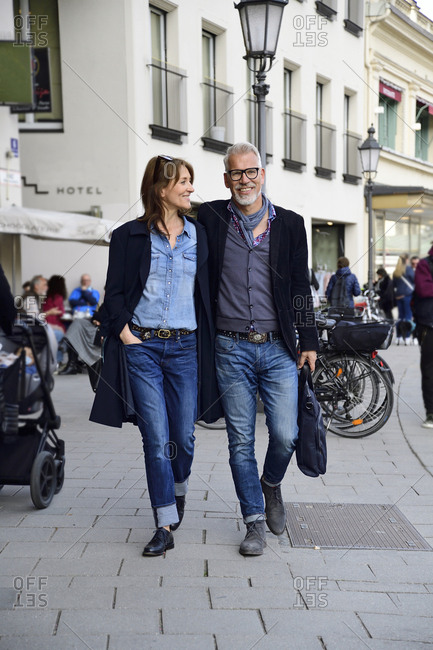 Mature couple walking in the city- with arms around