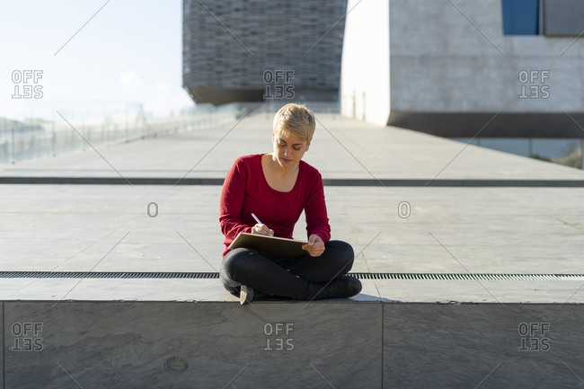 Young freelancer sitting outdoors using digital tablet