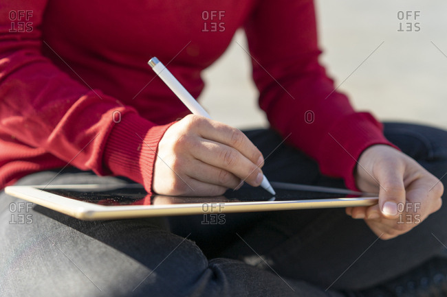Woman working on digital tablet- using stylus- close-up
