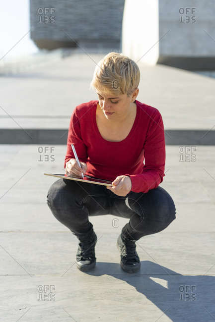 Young freelancer using digital tablet outdoors
