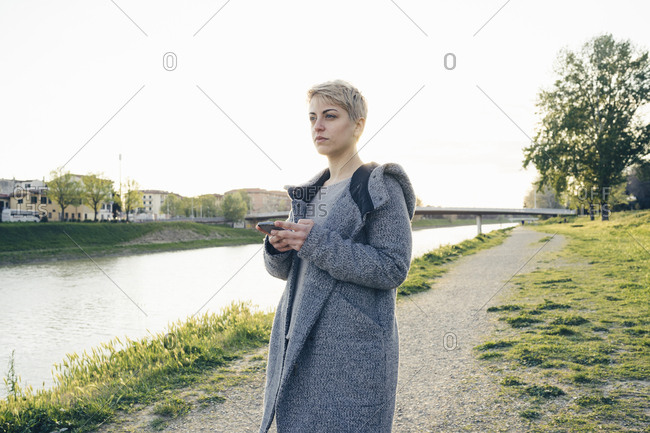 Young woman with cell phone outdoors looking at distance