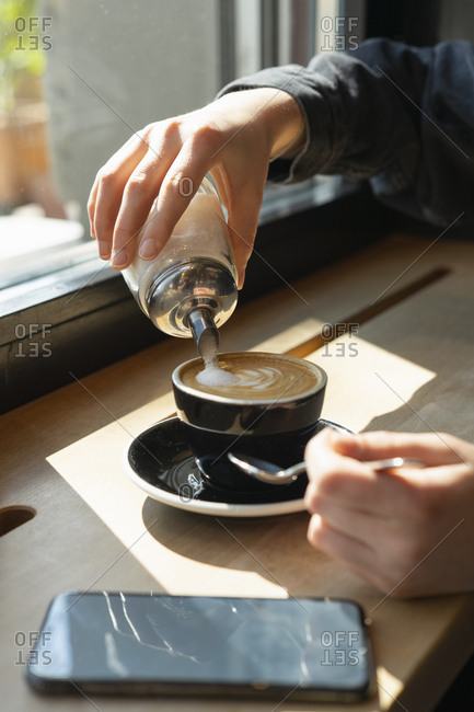 Woman's hand pouring sugar into cup of coffee
