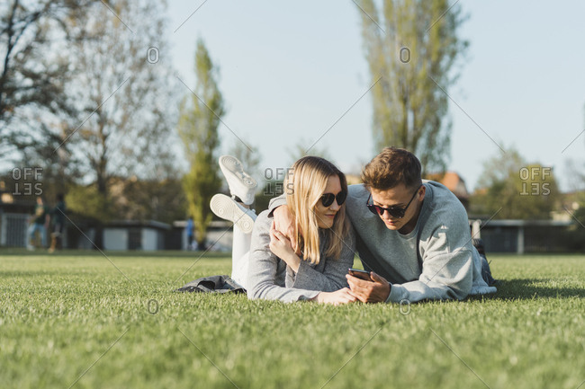 Young couple wearing sunglasses lying on a meadow looking at cell phone