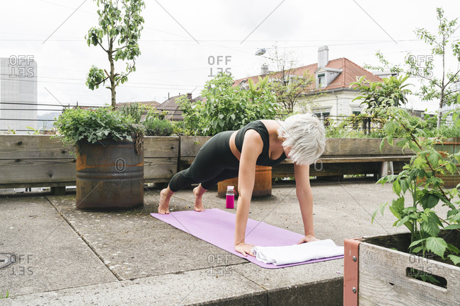Woman practising yoga on a roof terrace