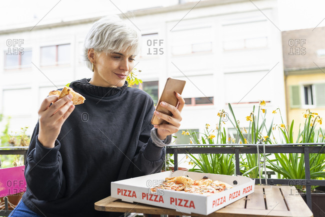 Woman eating pizza ina pizzeria- using smartphone