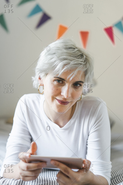 Portrait of smiling woman using cell phone on bed at home