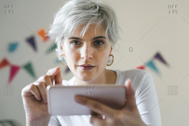 Portrait of woman using cell phone at home