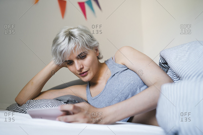 Woman lying in bed using cell phone