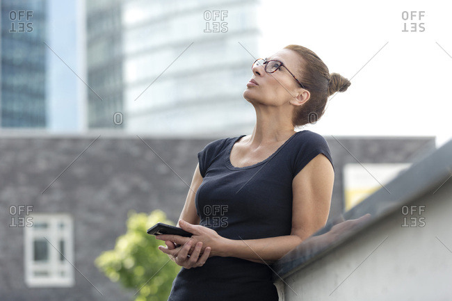 Woman with cell phone in front of office building looking up