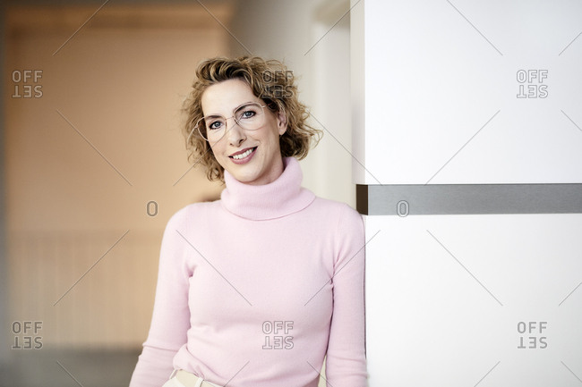Portrait of smiling businesswoman wearing pink turtleneck pullover and glasses