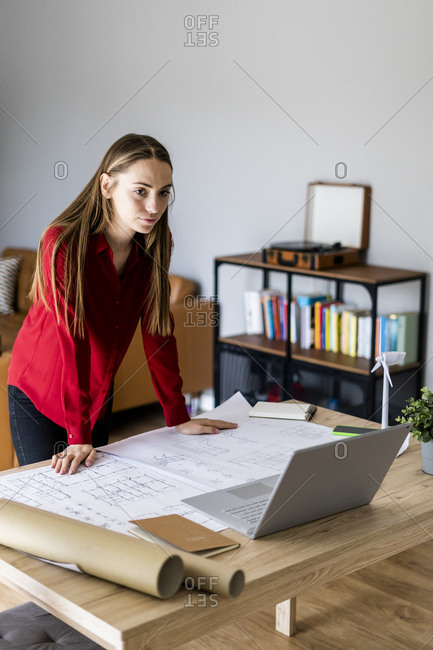 Woman in office working on plan with wind turbine model on table