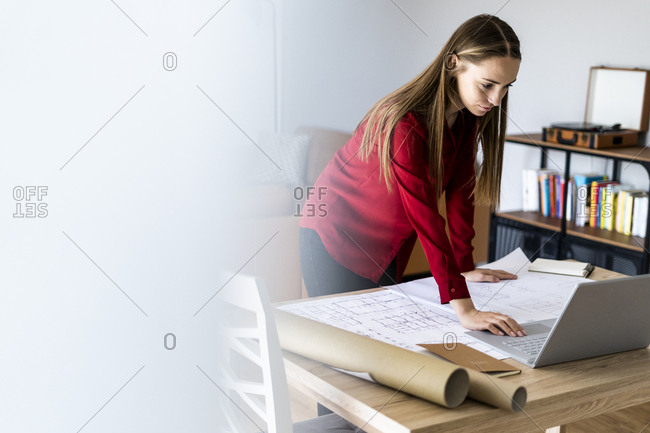 Woman in office working on plan and laptop on table