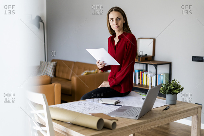 Woman in office holding paper with wind turbine model on table