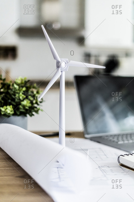 Wind turbine model- construction plan and laptop on table in office