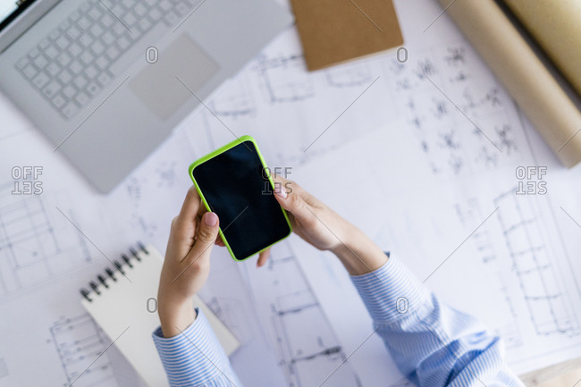 Close-up of woman in office using cell phone with blueprint on table