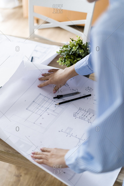 Close-up of woman in office working on plan on table