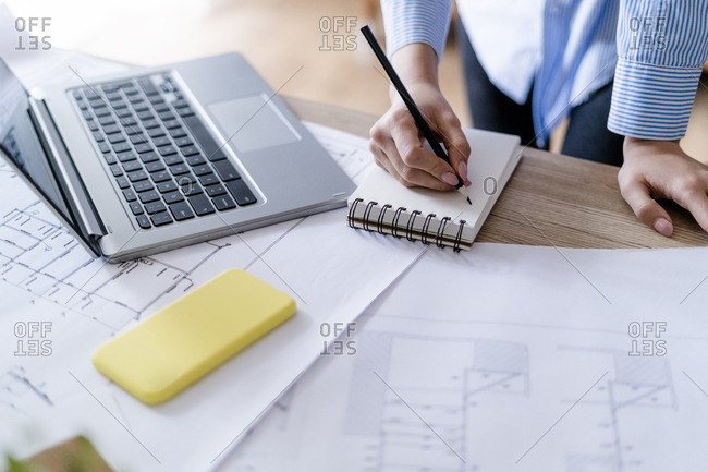 Close-up of woman in office taking notes with plan and laptop on table