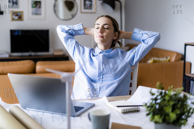 Woman in office leaning back with plan- laptop and wind turbine model on table