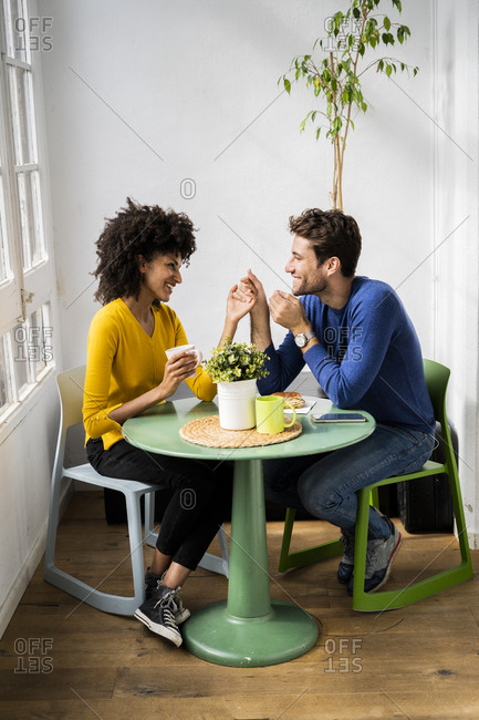 Happy affectionate couple sitting at table at home