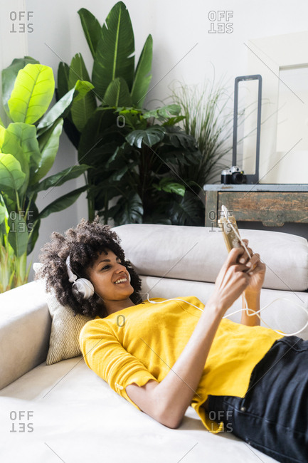Smiling woman lying on couch with cell phone and headphones