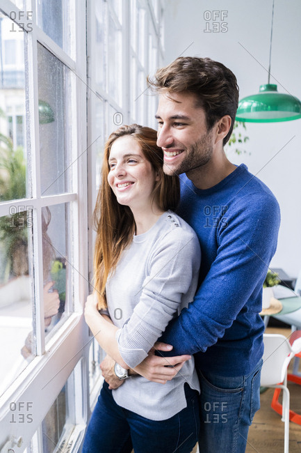 Happy affectionate couple hugging at the window at home