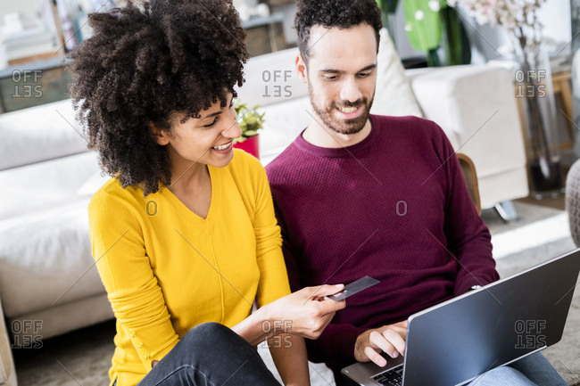 Happy couple at home shopping online with laptop and credit card