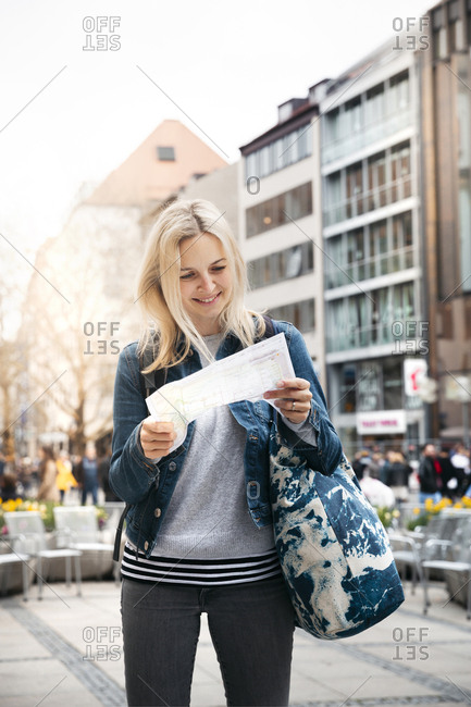 Portrait of smiling blond woman baggage looking at map in the city- Munich- Germany
