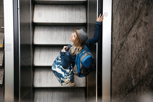 Woman with backpack and travelling bag standing on escalator looking up