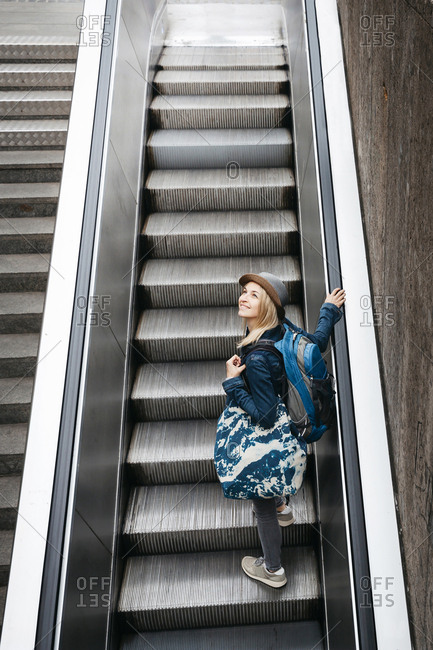 Smiling woman with backpack and travelling bag standing on escalator looking around