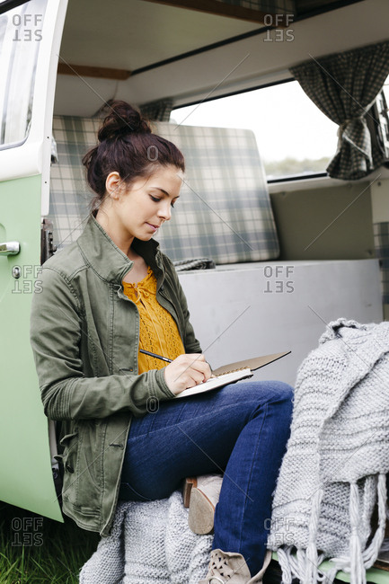 Young woman sitting in her camper- writing in a notebook