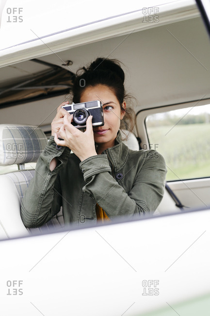 Young woman sitting in camper- taking pictures
