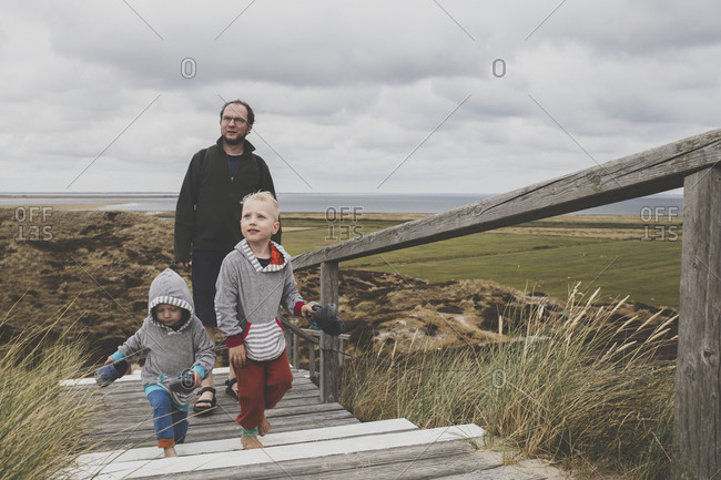 Father and his children walking up  stairs among the dunes- Sylt- Germany