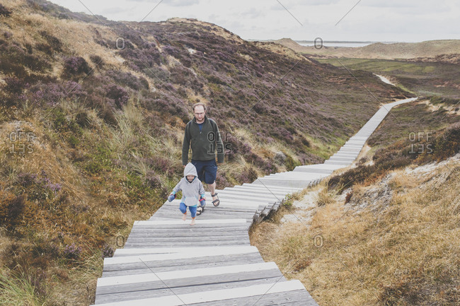 Father and little daughter walking up  stairs among the dunes- Sylt- Germany