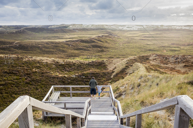 Back view of father and little daughter standing on viewing platform looking at landscape- Sylt- Germany