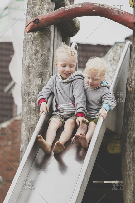 Two barefoot siblings together on a slide