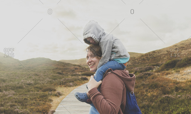 Portrait of smiling mother carrying little daughter on her shoulders- Sylt- Germany
