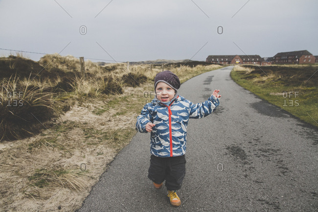 Portrait of little boy running on empty road- Sylt- Germany