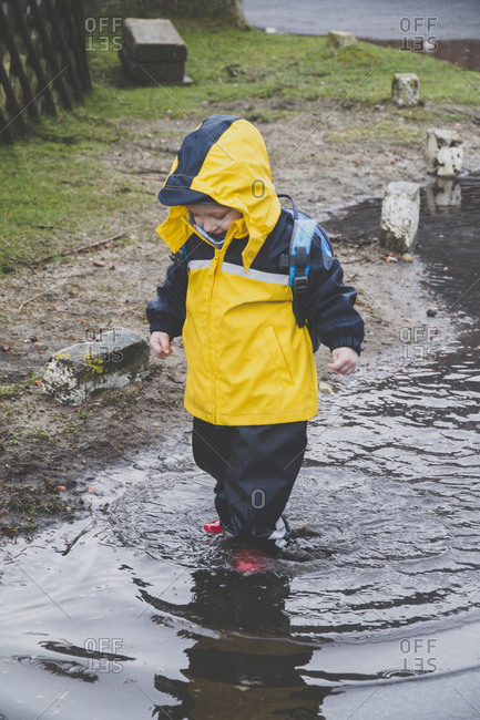 Little boy in a rainsuit exploring a puddle- Sylt- Germany
