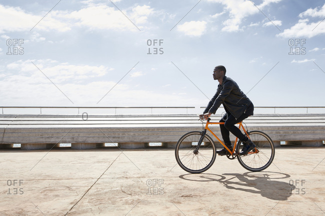 Man riding bike on waterfront promenade