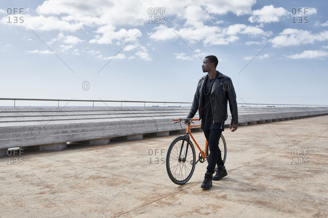 Man with bike on waterfront promenade