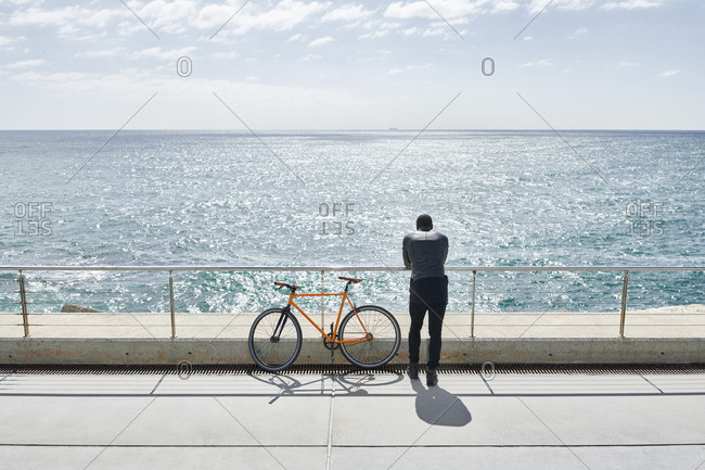 Rear view of man with bike on waterfront promenade