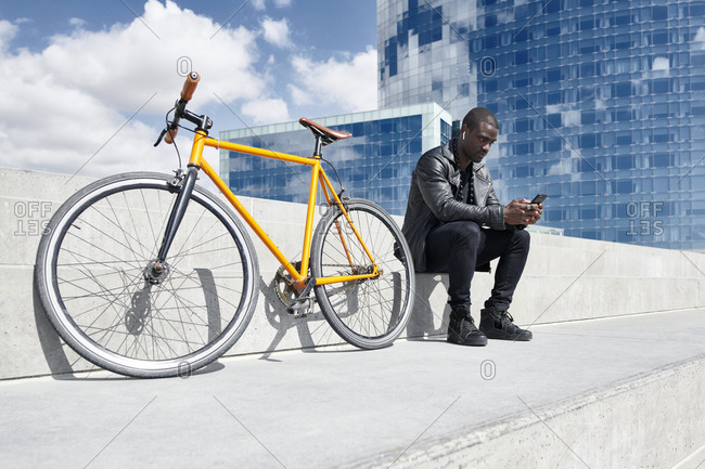 Man with yellow bicycle sitting on stairs- using smartphone- Barcelona- Spain