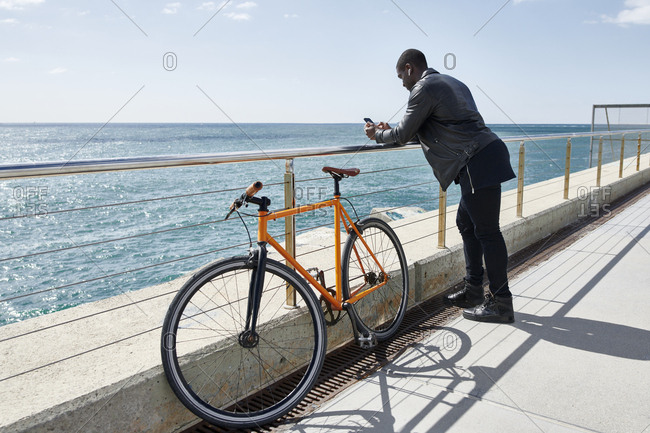 Man with bike on waterfront promenade- using smartphone