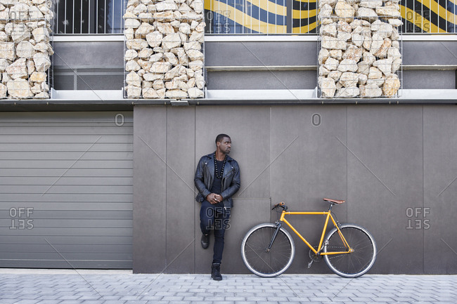 Man leaning on a wall next to his bike