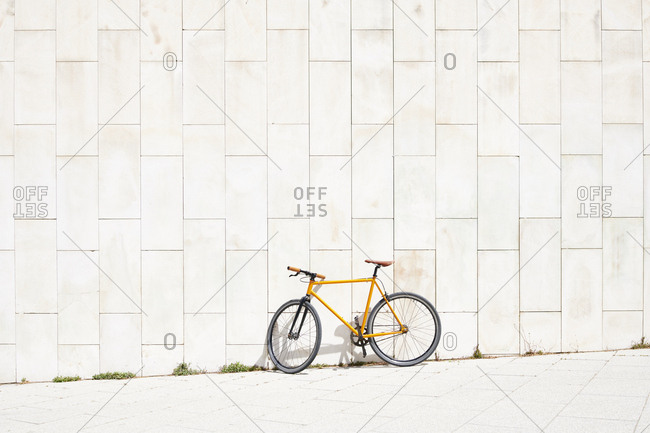 Bicycle leaning on concrete wall