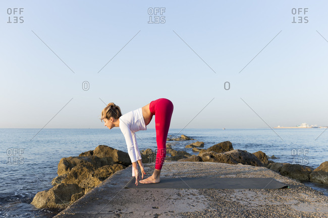 Young woman practicing yoga on the beach- doing sun salutations